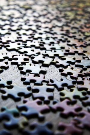 Puzzle pieces on a wooden table, reflecting only shapes, not colors.