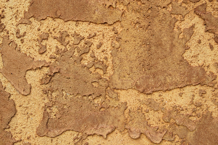 Roughly mudded stucco wall texture in rich brown.