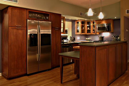 Modern kitchen with handmade cabinets and stainless steel appliances.