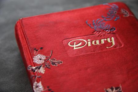Bestickt rot mit einem gut getragen Tagebuch.