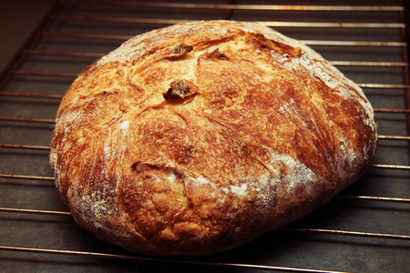 A loaf of hot, crisp artisan bread right out of the oven. Stock Photo