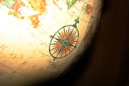 An ornate compass detail illustration on a large spinning globe. Stock Photo