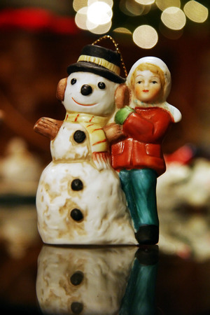Christmas ornament featuring a little girl and a happy snowman. Stock Photo