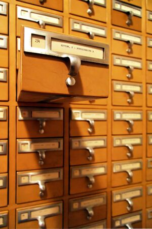 A large library card catalogue with one drawer open from the main cabinet. Stock Photo