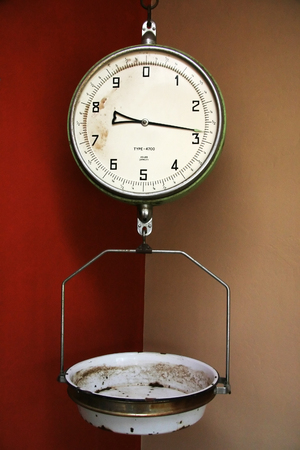 Old style grocery scale hanging a colorful corner of a room. Stock Photo