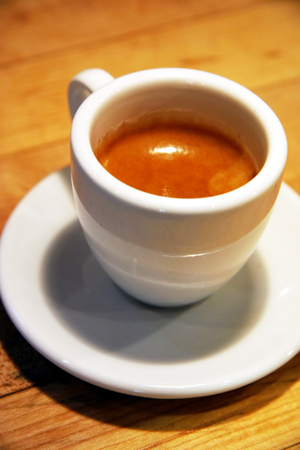 A single shot of espresso in a demitasse sits on the counter. Stock Photo