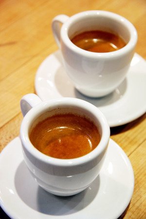 Two single shots of espresso with rich crema, sitting on the counter.