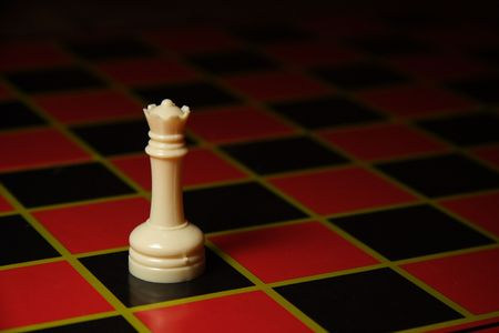 Lone queen sits on black and red chess board. Stock Photo
