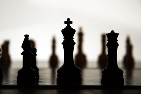 Chess pieces silhouetted against white light with opposing side in the distance. Stock Photo