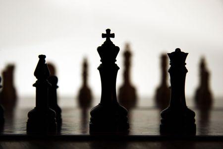 Schach St�cke silhouetted gegen wei�es Licht mit gegen�berliegenden Seite in der Ferne.  Lizenzfreie Bilder