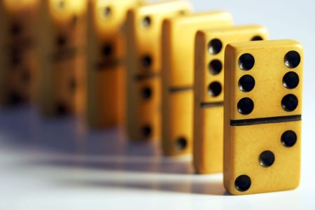 Very old vintage dominos lined up, ready to be tipped. Stock Photo