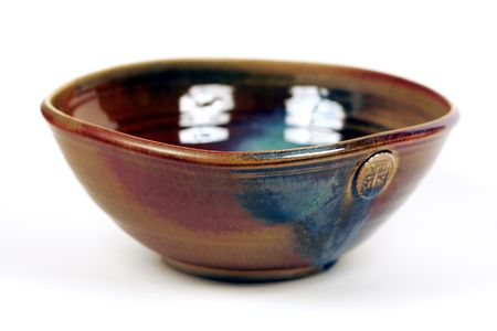 A medium size ceramic bowl with earth tone glaze. Stock Photo
