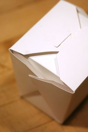 Folded paper take out container sitting on a counter.  photo