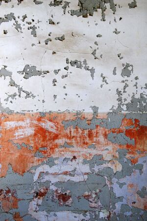 Old wall of peeling paint from abandoned building, white and red and orange. Stock Photo