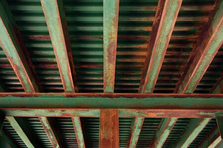 Rusting girders underneath a train trestle.