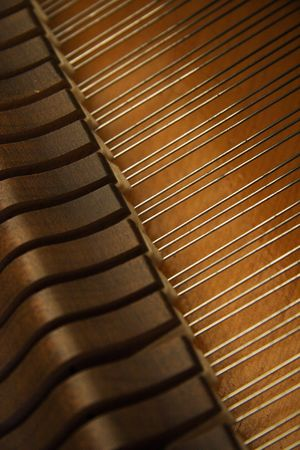 View of the strings and hammers inside a grand piano with the top open.