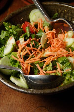 Fresh salad with carrots, cucumbers, lettuce and tomtoes, ready for serving with steel serving spoons.