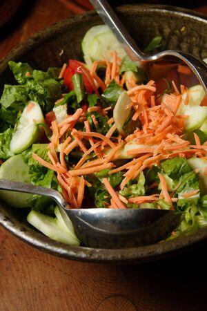 Frischer Salat mit M�hren, Gurken, Salat und tomtoes, bereit zum Servieren mit Stahl L�ffel serviert.