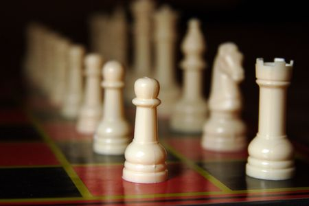 The white side of a chess set, lined up for the start of the game, fading into the distance.