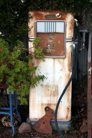 An old gas pump sitting with other relics as garden art. Archivio Fotografico