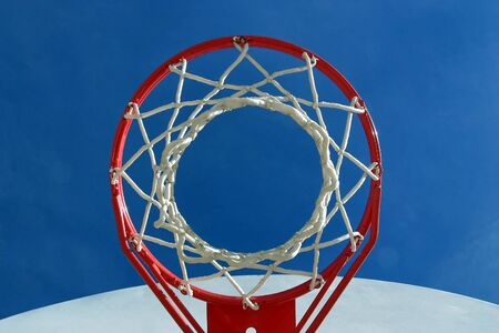 A basketball hoop, net and backboard on a playground, shot from below.