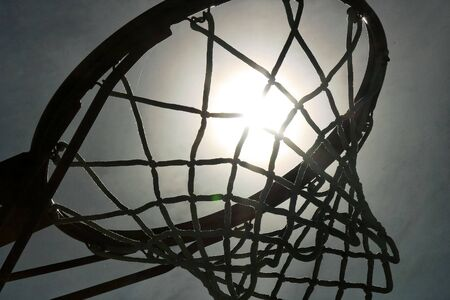 Silhouette of a basketball hoop, shot against the midday sun