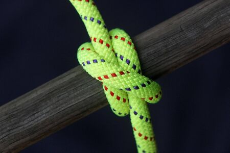 Bright green nylon rope tied around old wooden pole, clove hitch Stock Photo