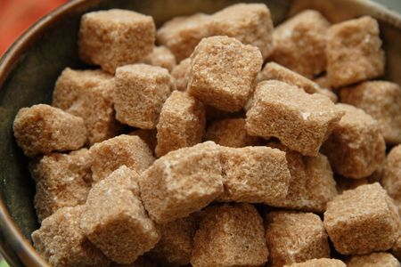 Cubes of unprocessed raw sugar in a bowl, ready for use