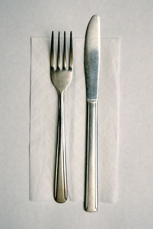 Cheap metal knive and fork on paper napkin, laid out for use Stock Photo