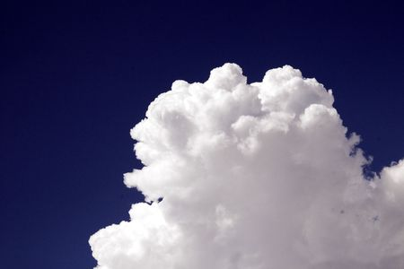 A perfect white cloud billows against a dark blue sky Stock Photo
