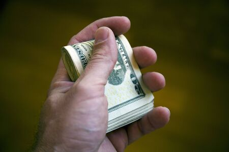 A hand holds a bundle of twenty dollar bills