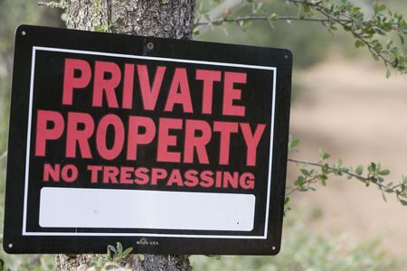 A sign screwed to a tree warns against trespassing on private property Archivio Fotografico