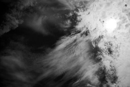 Black and white photo of textured clouds in a dark sky.