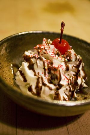 Small sundae with chocolate sauce, ice cream, cherry and sprinkles