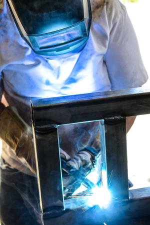 A welder in a face shield, working on a metal frame.