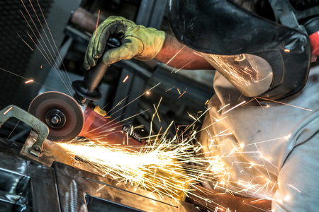 Man using angle grinder cut off wheel to section metal plate, with shower of sparks. Stock Photo