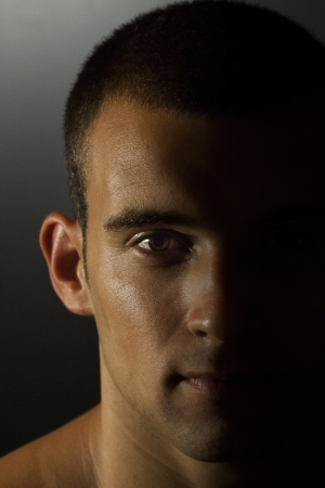 head close up: Young tanned man portrait with half face iluminated