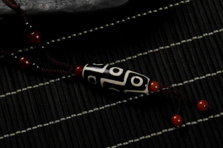 Tibetan 9 Eyes Dzi Beads necklace.Tibet Antique Buddhist Old Necklace Pendant. Tibet amulet. Dark background with incense sticks