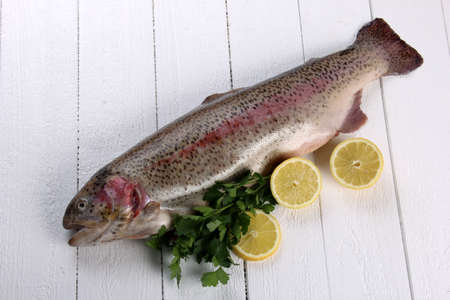 Whole Rainbow trout fish on a white wooden background. Raw trout with lemon and spice