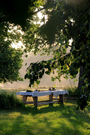Outdoors summer scene party table on sunset. Old wooden table under trees with food plate. Midsummer celebrating in Latvia, Ligo festive Banque d'images