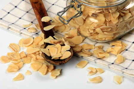 Dried garlic flakes on white background. Dried vegetables Imagens