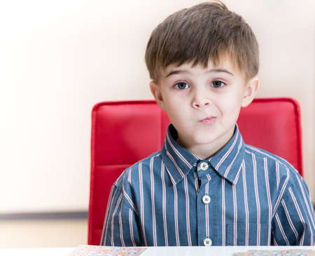 pre adolescent boys: puzzled little boy at the table Stock Photo