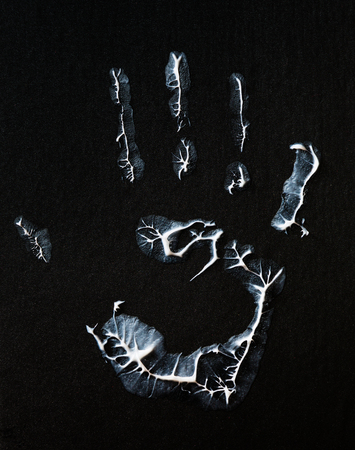 imprint: fat human hand imprint on black background, vertical photo