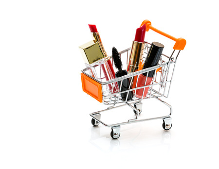 carretilla de mano: Makeup in pushcart isolated on white background.