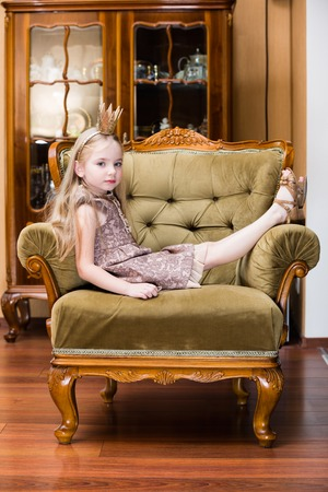little girl blond hair wearing crown standing at the chair.