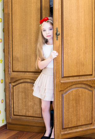 baby wardrobe: Little girl in mothers shoes near the wardrobe