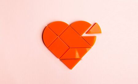 jigsaw tangram: Plastic puzzle in the form of heart with disconnected piece on a pink background