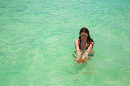 Wet young woman with super long hair in turquoise sea water holding big starfish in hands
