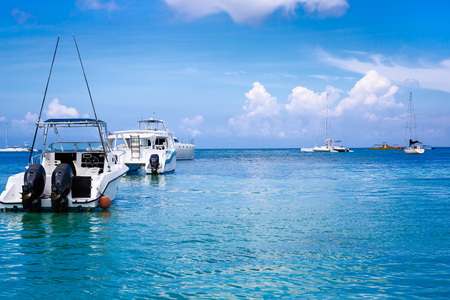 trat: Boats in the Caribbean. A saturated blue sky, clouds and the sea.