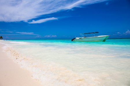 secluded: cutter on tropical beach with blue water background